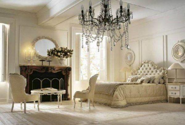Искусственные белые цветы в белой вазе красиво сочетаются с общим интерьером спальни