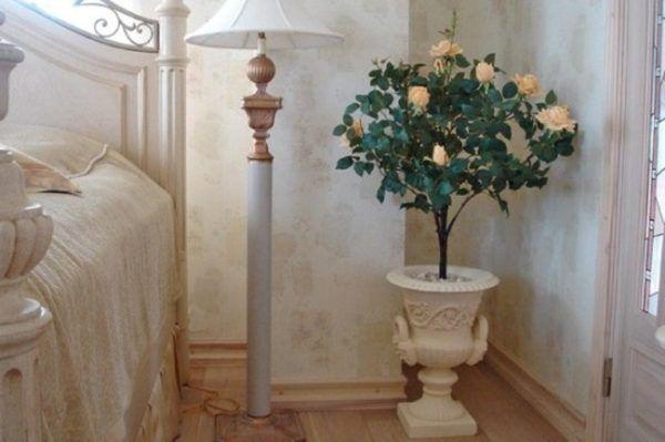 Искусственные цветы в напольной вазе в спальне