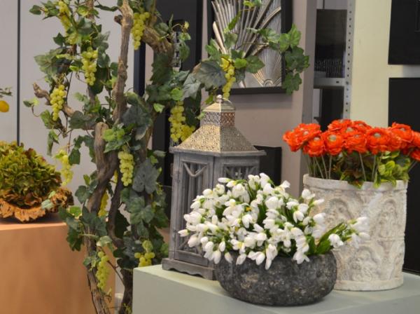 Искусственные цветы и ветвь виноградной лозы с плодами