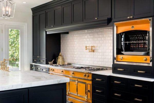 Яркие акценты оранжевого в классической черно-белой кухне
