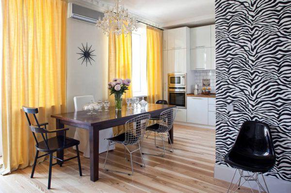 Яркие желтые шторы оживляют темно-белый интерьер кухни