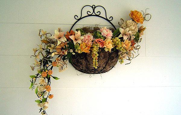 Искусственные цветы с фруктами в подвешенной корзине