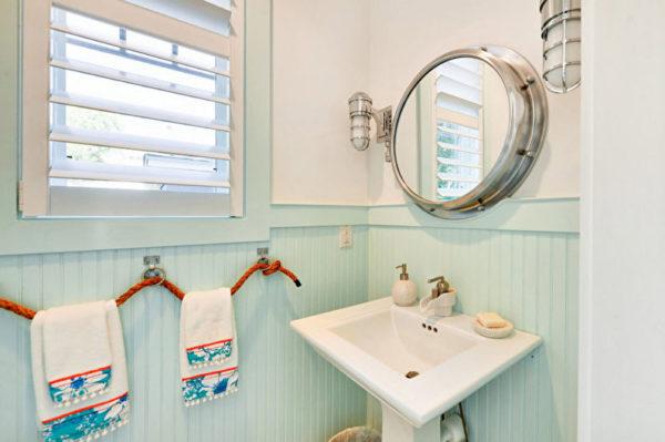 Круглое зеркало и освещением отлично вписывается в интерьер ванной комнаты