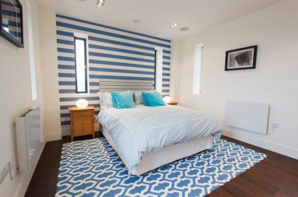 Оформление одной стены в бело-синюю полоску в средиземноморской спальне